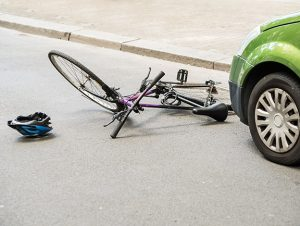 image of bicycle crashed in front of car