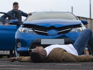man laying in front of car after being hit